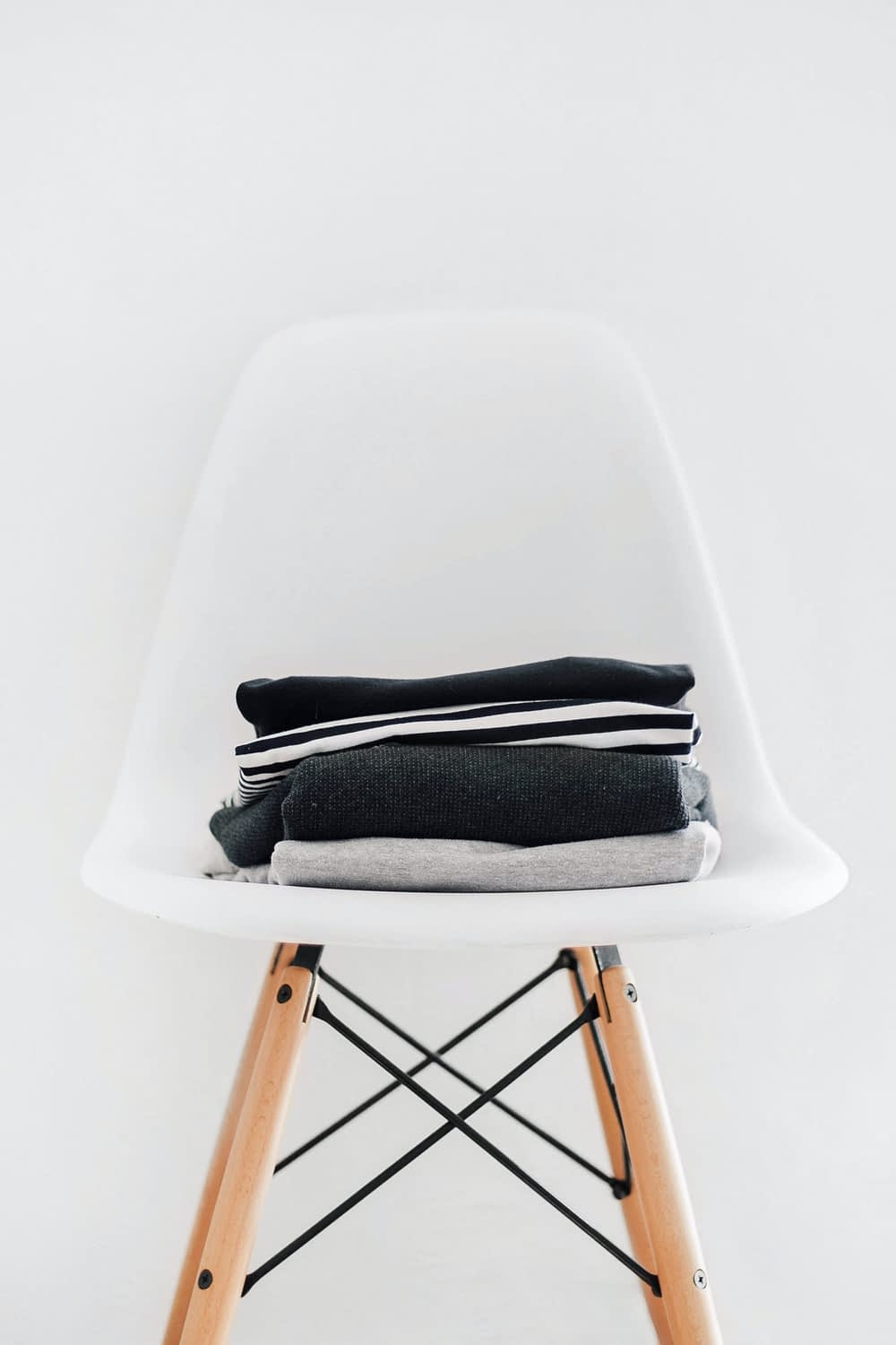 pile of black, white, and gray textiles on white padded chair with brown frame